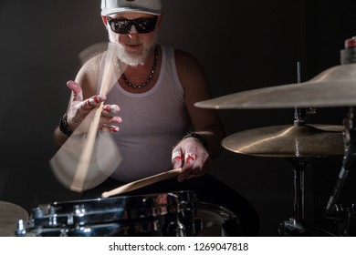 The old drummer twists a stick