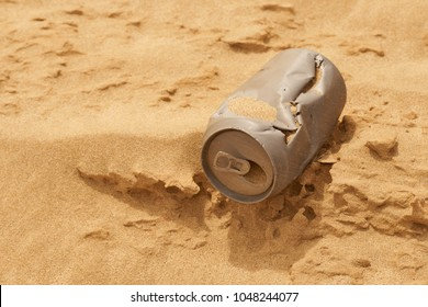 Old dry and discarded can in desert sand with inscriptions 'don't litter' and 'please recycle'
