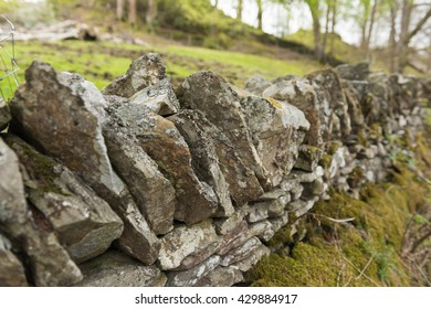 Old dry stone wall in the english countryside vanishing into the distance, with shallow depth of field