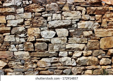 Old dry stone wall of a rural traditional house