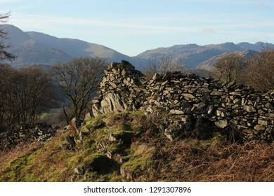 Old drystone wall lit with afternoon sun, Loughrigg fell, the Lake District England, with Coniston and Crinkle Crags in the background