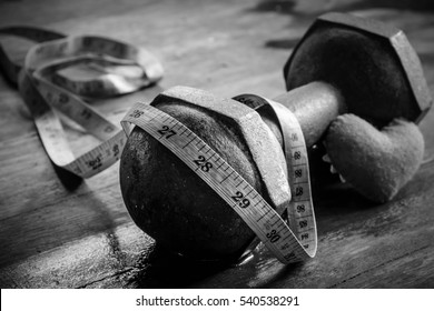 Old dumbbell with measuring tape and red heart on wooden table,Sport equipment,Healthy lifestyle concept,Still life photography,Black and white