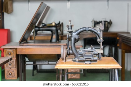 Old and Dusty Black Round Sewing Machine in Vintage Style on Wooden Table. No in used and now used for Decoration.