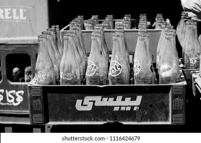 Old dusty glass bottles of cocacola, fanta and sprite (written in Arabic and English) in plastic containers with word Pepsi written on it in Arabic. Cairo, Egypt. March 2018