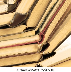 old dusty opened books stack on table, sepia toned