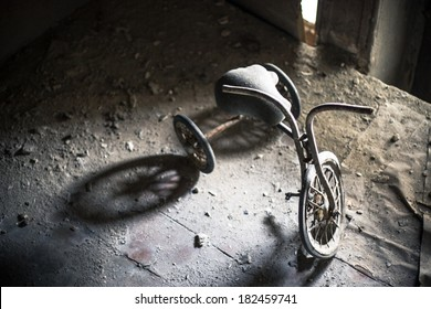 Old dusty tricycle standing on the wooden floor