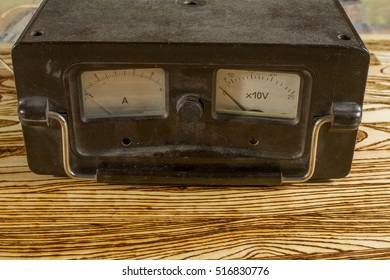 The old dusty voltmeter and the ampermeter costs on the wooden desktop.