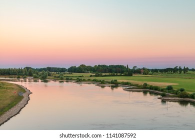 The old Dutch river IJssel in the province of Gelderland near the city of Zutphen during sunset