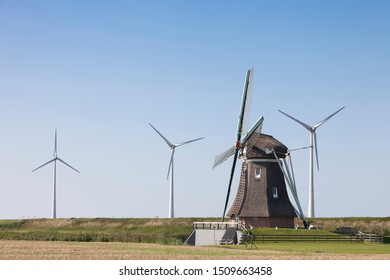old dutch windmill and modern wind turbines against blue sky in dutch province of groningen near eemshaven in the netherlands