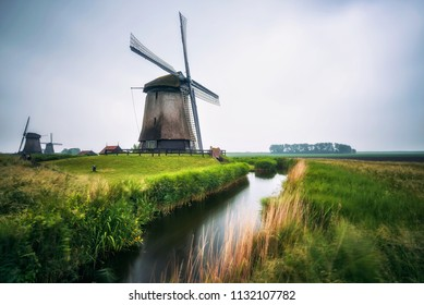 Old dutch windmills with a stream flowing by in cold morning scenery near Amsterdam, Netherlands. Long exposure.