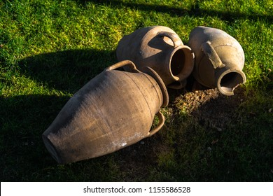 Old earthenware jars on grass lawn.