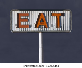 Old eat sign with storm sky.