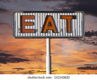 Old eat sign with sunset sky.
