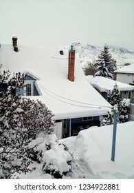 An old eclectic  house covered in fresh fluffy white snow during the winter in Kamloops, British Columbia, Canada.