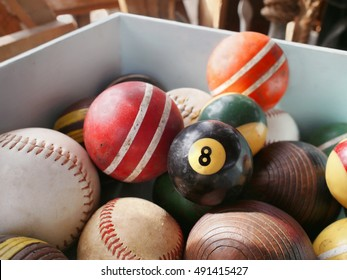 An old eight ball in wooden bin full of vintage game balls, including pool, croquet, and baseball.