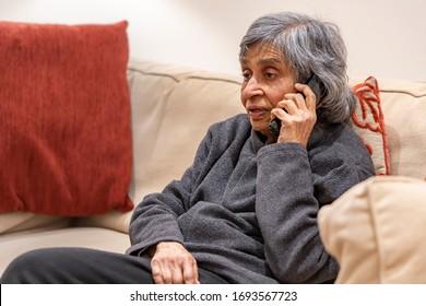 Ancianos mayores, mujeres británicas asiáticas hablando por teléfono, auto aisladas durante el bloqueo de brotes de coronavirus en el Reino Unido