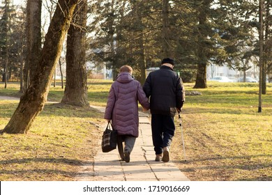 old elderly couple retired spouses walk in the park holding hands. the old man has a cane in his hand. Minsk, Republic of Belarus. 04/27/2020