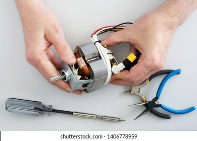 Old elderly home craftsman repairs the electric motor from  mincer. Home closeup  shot