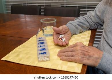 Old elderly man sorting medication