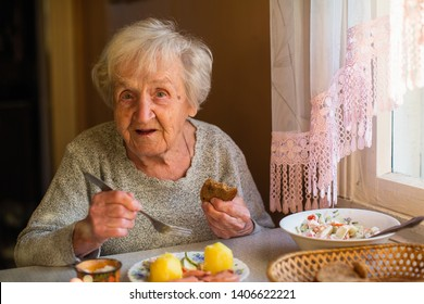 An old elderly woman eats sitting at the table in his home.