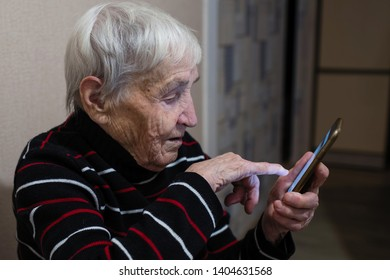 Old elderly woman pensioner typing on a smartphone.