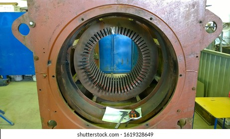 Old Electric motor repair. Winding replacement. Welded steel housing, stator core. Workshop at the Industrial plant. Dirty rusty metal surface, damaged texture. Rotating machine services.