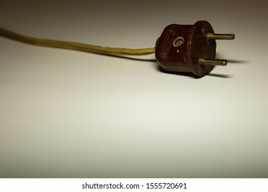 An old electric plug with a cord on a light muted background.