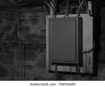 An Old Electrical Box with Mold in an Old Stone Foundation Basement, Interior, Interior Illumination, Medium Shot, Eye Level, Stone Foundation Wall in Background.