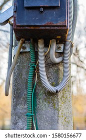Old electrical panel on a concrete pillar. Metal shield with many connected high voltage cables. Selective focus. The vertical arrangement of the photo. Without people.