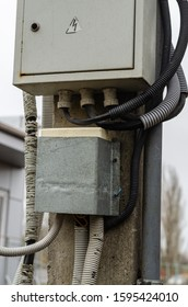 An old electrical panel, a rusty metal box hangs on the shield of an electric pole. Electric cables in protective corrugations. Selective focus. Without people. The vertical arrangement of the photo.