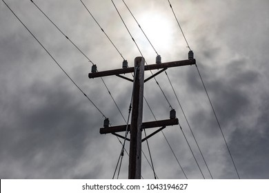 An old electrical pole shot on a stormy day with storm clouds overhead. The dated electrical network has rust, but is the source of electricity for a town in New England. The wires run above ground.