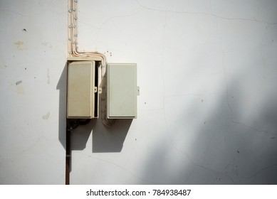Old Electronic control on the white cement wall. Outdoor installation And sunshine through the top of tree hit the wall.