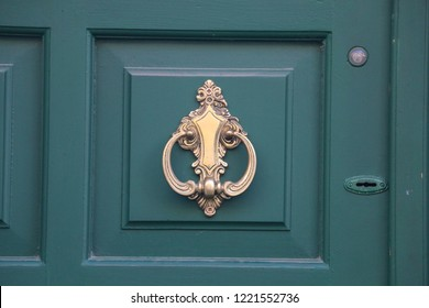Old elegant golden metal door handle, knocker