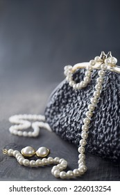 Old elegant vintage handbag from the 1950's with luxury pearls on black background for copy space