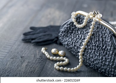 Old elegant vintage handbag from the 1950's with luxury pearls and earrings on black background for copy space