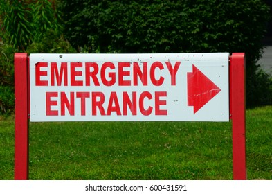 "Old ""Emergency Entrance"" sign on hospital lawn."