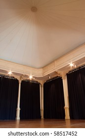 Old empty ballroom with wooden floor, curtains, spotlights and amazing dome ceiling.