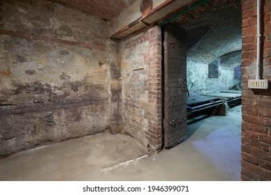 Ancien sous-sol vide avec murs en briques et portail en bois