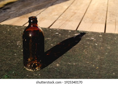 Old empty beer bottle on grungy outdoor deck carpet
