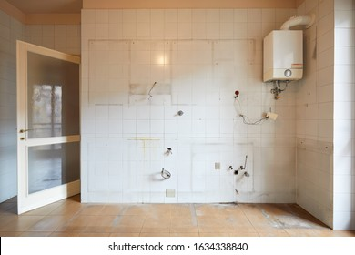 Old, empty kitchen wall with white, dirty tiles in apartment interior