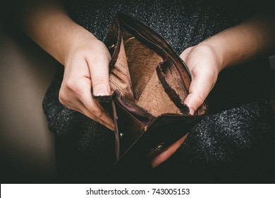 Old empty wallet in the hands .Vintage empty purse in hands of women . Poverty concept, Retirement. Special toning