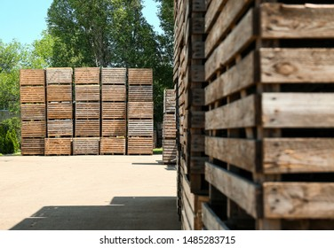 Old empty wooden crates outdoors on sunny day. Space for text