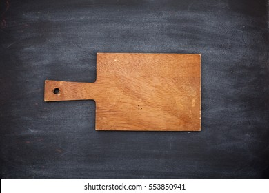 Old empty wooden cropped cutting board on black background from chalkboard. Close up. Top view. Flat lay. Mock up for restaurant menu.