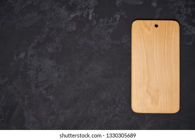 Old empty wooden  cutting board on black background, top view