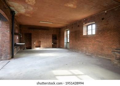 Vieux atelier vide avec murs en briques rouges, lumière du soleil