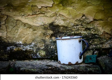 Old enamelware mug against a grungy wall
