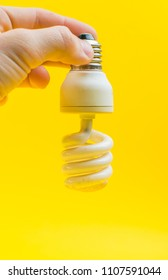 old energy-saving lamp in hand on yellow background