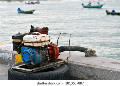 Old engine for pumping seawater with blurred ocean and fishing boat background.