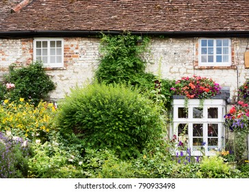 Old english cottage house with wild flower garden, view of facade with windows and plants.