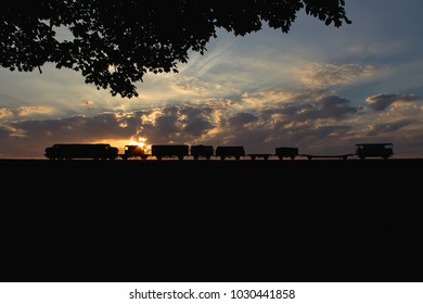 An old English diesel-electric locomotive and its train, seen at sunset, as a silhouette against the evening sky.
